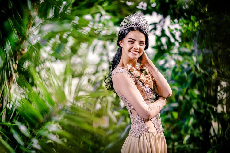Portrait Of Beautiful Bride Wearing Crown While Standing Amidst Plants At Botanical Garden