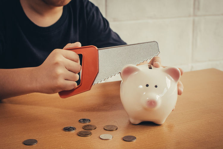 Midsection of man cutting piggy bank with hand saw on table
