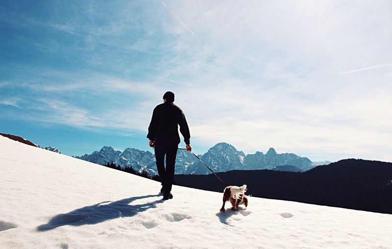 Rear view of man with dog on snow covered mountain against sky