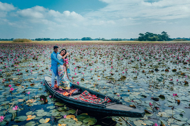 View of people standing in waterlily pond against sky