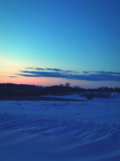 Scenic view of frozen landscape against blue sky