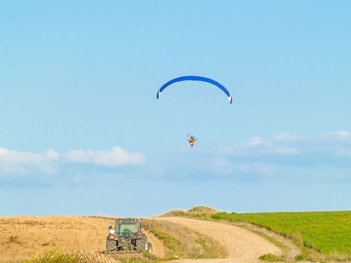 Person powered paragliding over agricultural field against blue sky