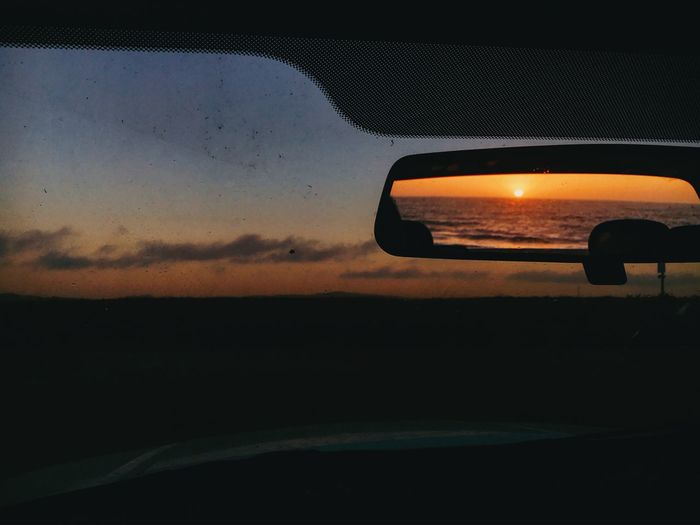 Sunset in the rear view California Coast California Pacific Ocean West Coast Moving Forward  The Past Copy Space Rearview Mirror Sky Car Transportation Sunset Mode Of Transportation Motor Vehicle Nature Scenics - Nature Beauty In Nature Car Interior Night Window