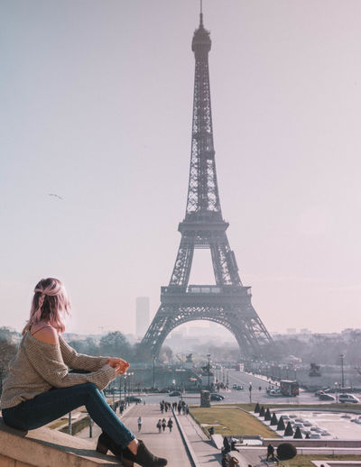 Woman looking at eiffel tower against sky