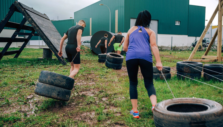 Rear view of friends pulling tires on land