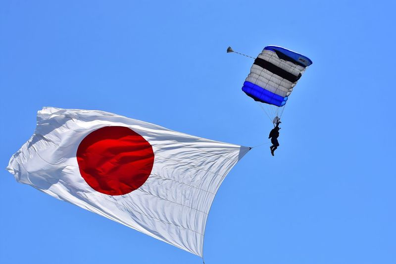 Low angle view of paraglider paragliding with japanese flag
