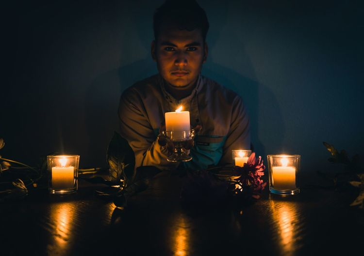 Portrait of young man sitting with candles in darkroom