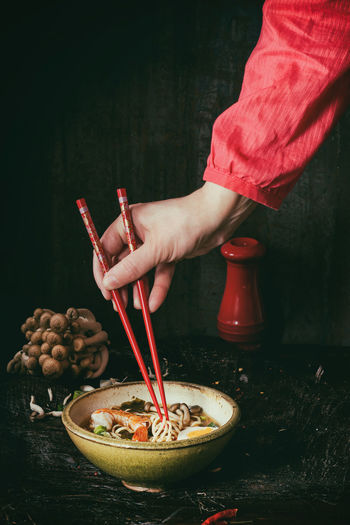 Female hand in red shirt take by red chopsticks noodles from asian ramen soup with shrimp, onion, sliced egg and mushrooms, served in bowl over wooden table. Dark rustic style. Retro filter effect Asian  Asian Dish Dinner Hands Ingredients Red Seafood Shrimp Woman Asian Food Chopsticks Dark Photography Egg Female Mushroom Onion Ramen Ramen Bowl Ramen Noodles Ready-to-eat Rustic Style Soup Table Tofu Wooden