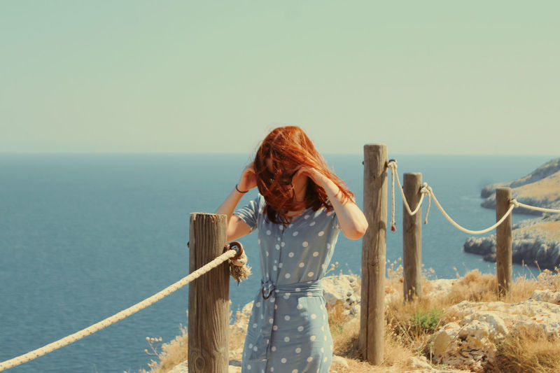Woman looking at sea against clear sky