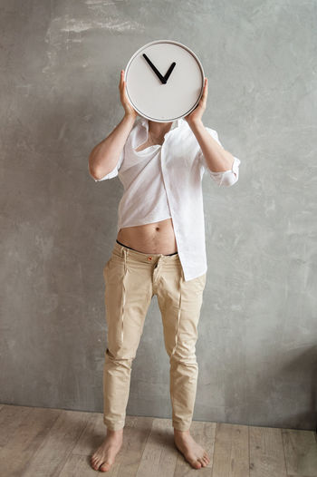 Full length of man holding umbrella standing against wall