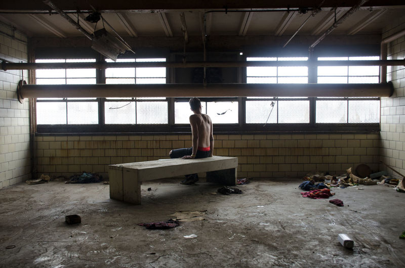 Rear view of shirtless man sitting in abandoned room