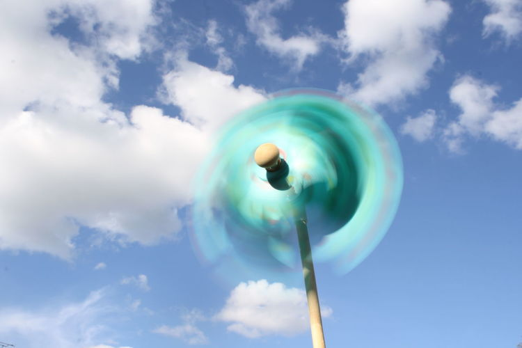 Close-Up Of Spinning Pinwheel Against Cloudy Sky