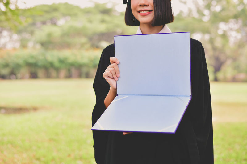Midsection of young woman in graduation gown holding file while standing at park