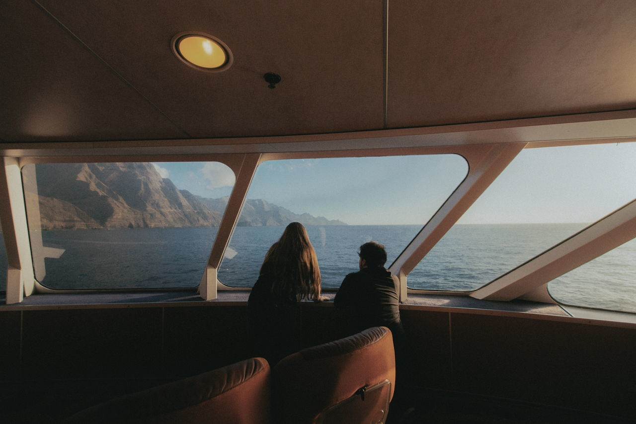 Rear view of man and woman leaning by window in boat