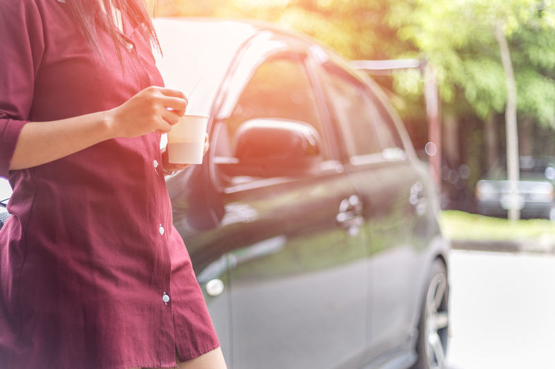 Woman holding disposable cup of coffee beside car Adult Adults Only Car Colors Day Human Body Part Human Hand Lifestyles Mode Of Transport One Person One Woman Only Outdoors Pattern People Pink Color Real People Relax Standing Transportation Travel Destinations Wait Women Young Adult