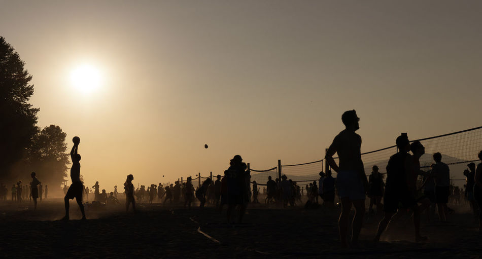 Silhouette people playing volleyball at beach during sunset