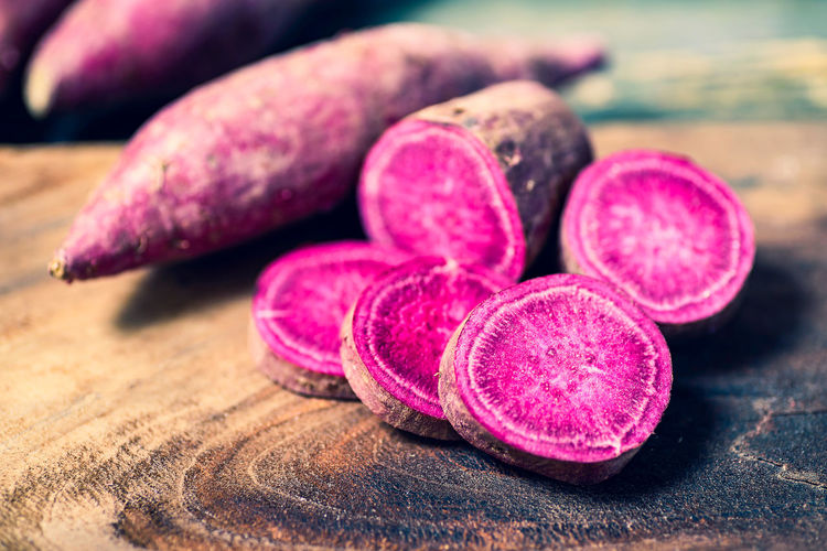 Agriculture Color Cooking Crop  Food Fresh Freshness Health Healthy Ingredient Nature Nutrition Organic Piece Potato Purple Raw Root Sliced Sweet Tuber Vegetable Vegeterian Wood Healthy Eating Wellbeing Indoors  Table Fruit Root Vegetable SLICE Wood - Material Raw Food Pink Color Close-up Selective Focus