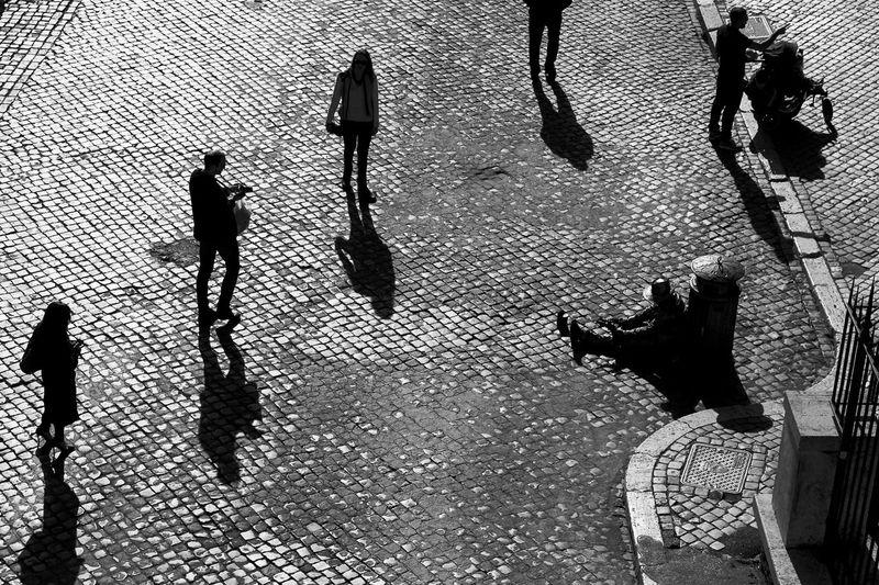 Pflastersteine in Rom. Ein Straßenkünstler macht Pause und die Menschen laufen über den Platz. Platz Pflastersteine KopfSteinPflaster Castel Sant'Angelo Rom Walking High Angle View Street Real People Outdoors Silhouette Shadow City Lifestyles Men Women First Eyeem Photo Stories From The City Stories From The City