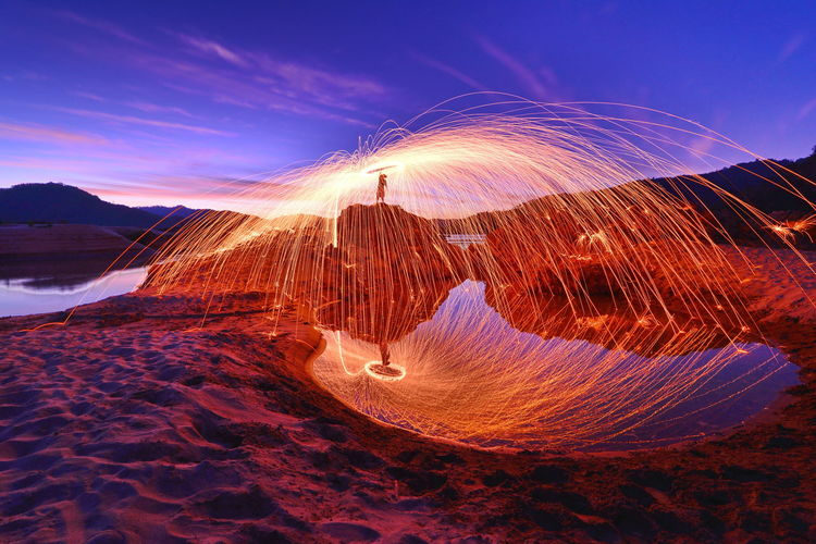 Person With Wire Wool Against Sky During Sunset