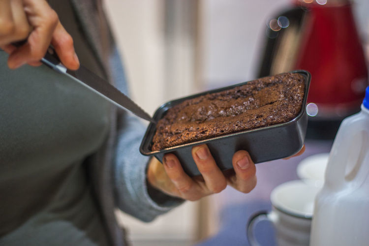Midsection of woman cutting chocolate cake at home