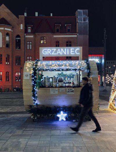 Blurred motion of people on illuminated street at night