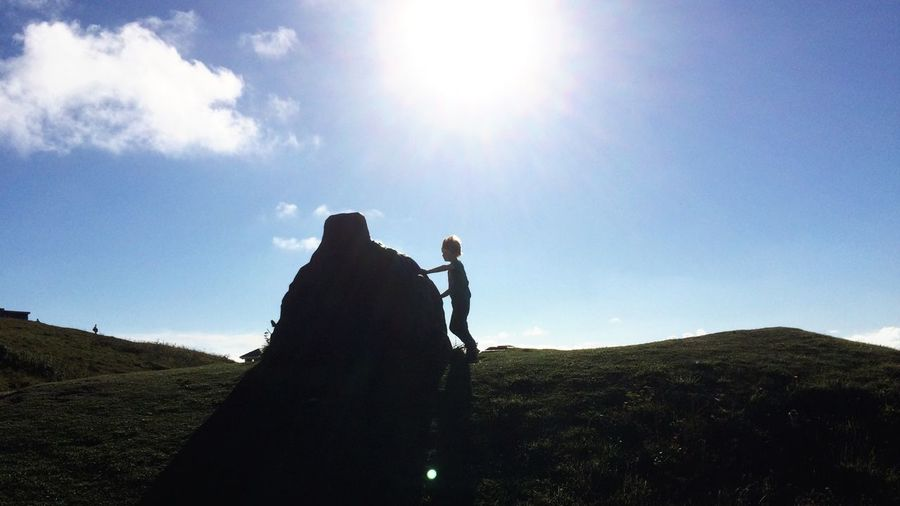 Boy Touching Stone On Field Against Sky During Sunny Day