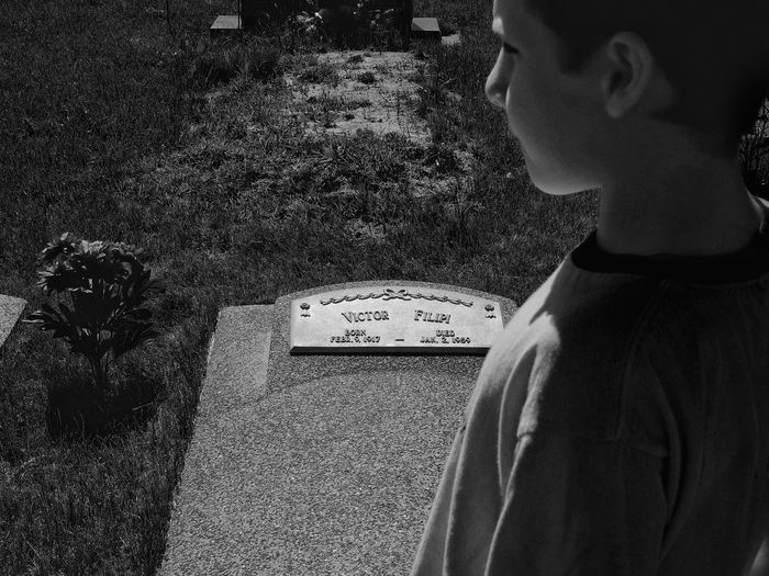 High angle view of boy at tombstone in cemetery