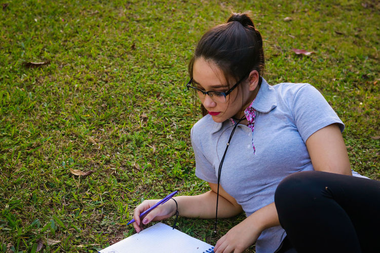 High angle view of young woman studying at park