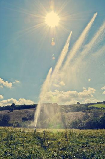 Sprinkler On Grassy Field Against Sky