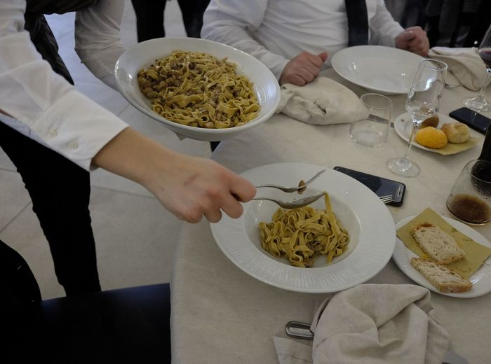 Low Section Of Waiter Serving Pasta In Bowl At Restaurant