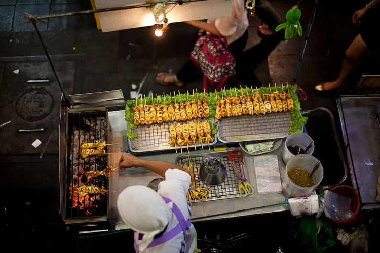 High angle view of man cooking squid at market stall