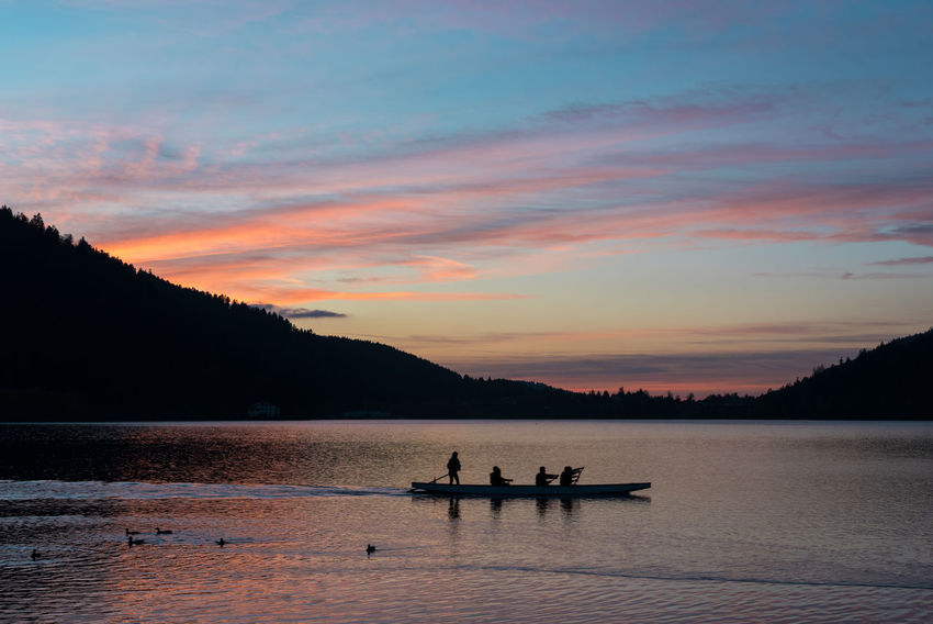 Sunset Landscape Lake Real People Healthy Lifestyle Kayak Kayaking Water Canoe Canoeist Canoeing Water Sport Mountain Sky Nautical Vessel Beauty In Nature Transportation Scenics - Nature Cloud - Sky Mode Of Transportation Silhouette Nature Tranquility Waterfront Tranquil Scene Orange Color Tree Non-urban Scene Outdoors