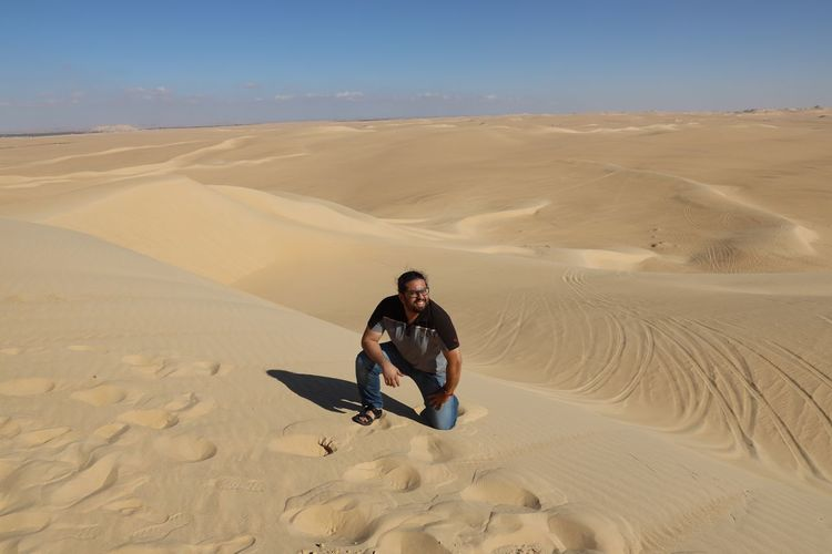 Full length of man kneeling on sand dune in desert