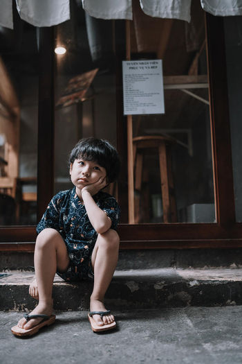 Sad boy looking away while sitting on footpath