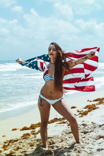 Woman holding american flag at beach against sky