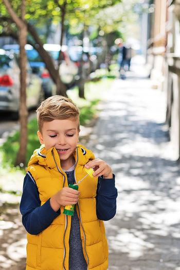 Boy holding umbrella standing on street