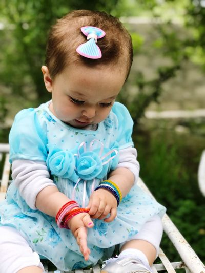 Cute baby girl sitting outdoors
