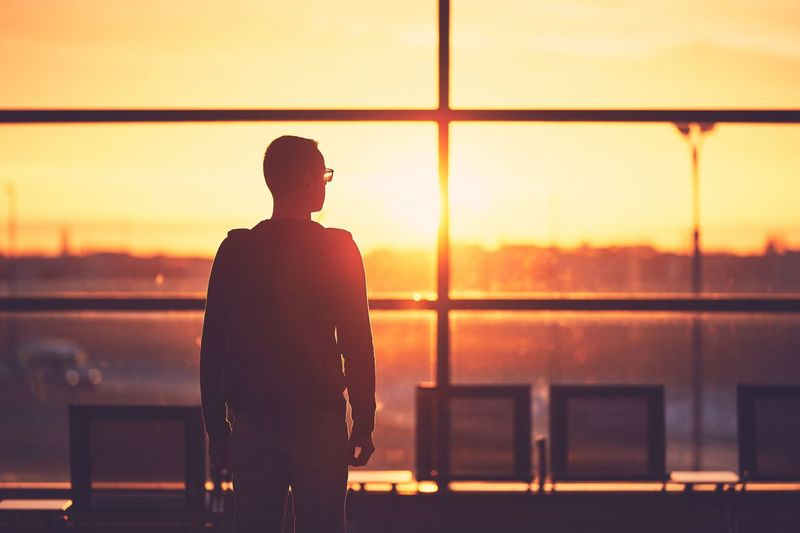 Rear view of man standing at airport during sunset