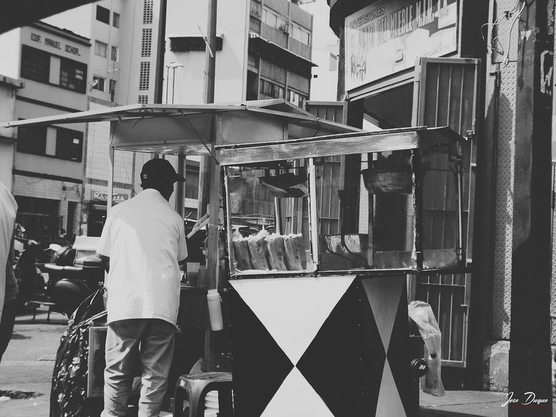A COMER COTUFAS...!!! Black & White Blackandwhite Building Exterior Caracas City Day Fujifilm Manual Worker Men Occupation One Person People Real People Rear View Standing Street Streetphotography Transportation Urban Venezuela Working The Street Photographer - 2017 EyeEm Awards EyeEmNewHere The Photojournalist - 2017 EyeEm Awards