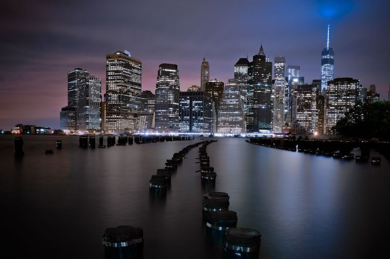 Wooden posts amidst river against cityscape at night