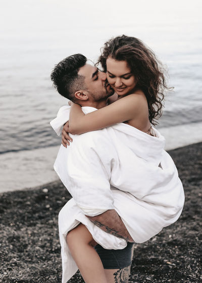 A diverse of lovers a man and a woman embrace under a blanket on the ocean at night outdoor