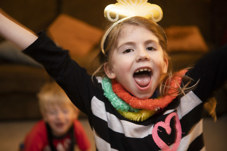 A seven-year-old girl raises her arm in celebration of New Year's Eve at her house. Happiness Smile Journey Party Celebration New Year's Eve New Year's Eve 2019 Joy Joyful Girl Family Siblings Arms Raised Tongue Out Indoors  Lifestyles Leisure Activity Two People Positive Emotion Moments Of Happiness