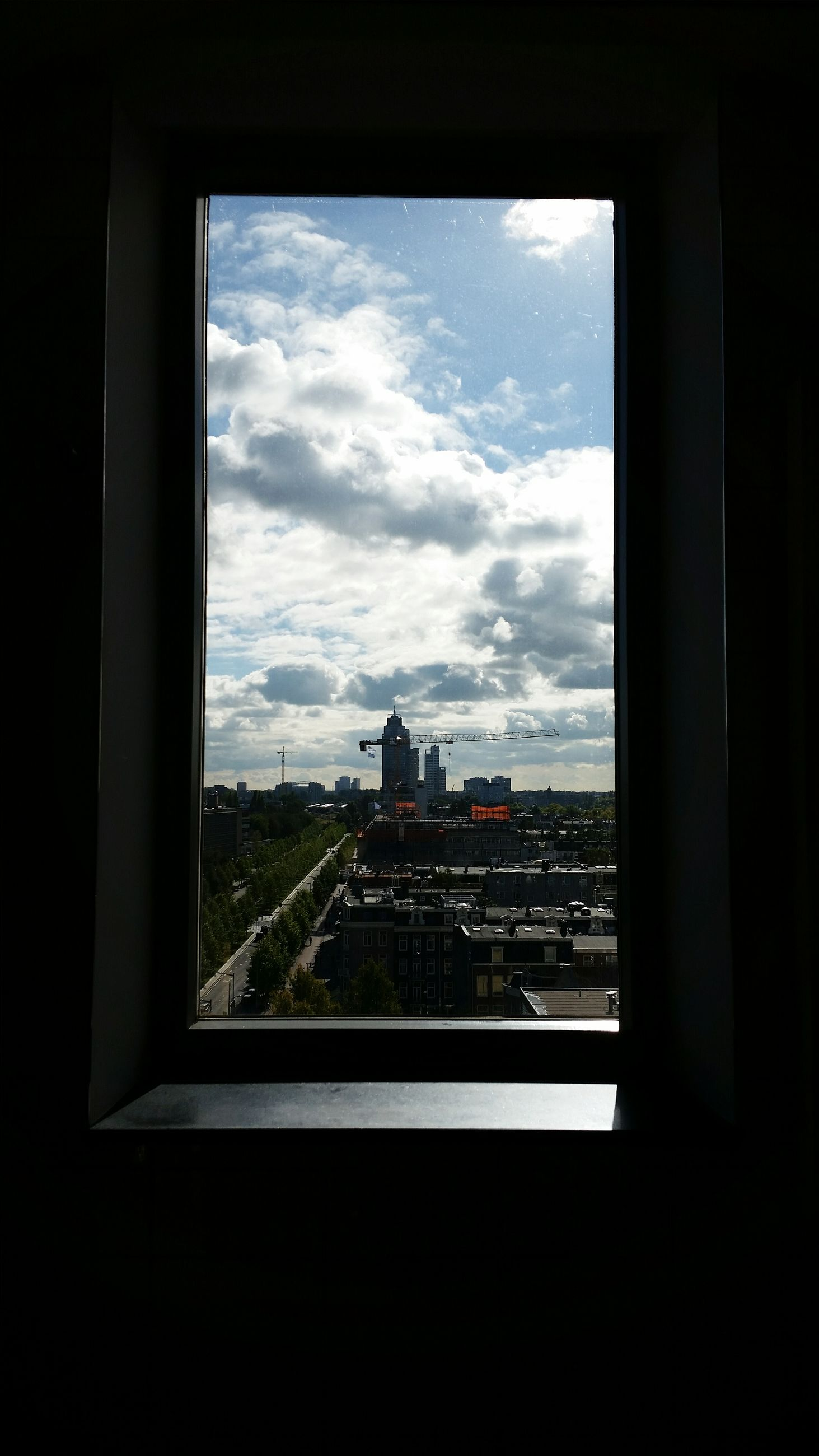 window, indoors, sky, cloud, built structure, architecture, city, transparent, cloud - sky, glass - material, building exterior, cityscape, day, cloudy, cloudscape, development, city life, tall