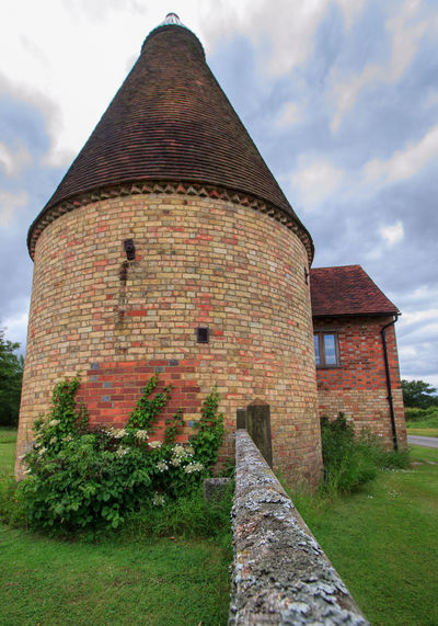 Oast House,Garden of England, Kent, England. Plant Nature No People Built Structure Architecture Building Exterior Outdoors Building Hops Beer Brewing Travel Destinations Tourism Caravan Rural Scene Countryside EyeEm Gallery Vivid International Getty Images Architecture Iconic Buildings Sky Cloud - Sky Grass History The Past Day Old Field Land Wall Low Angle View Brick Stone Wall