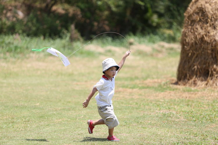 Full length of boy playing on grass