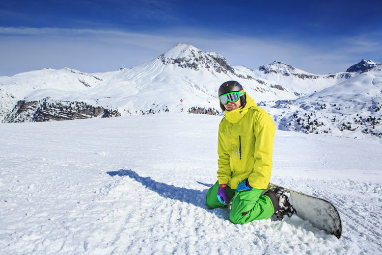 Portrait Of Smiling Young Man Skiing On Snowcapped Mountains During Winter