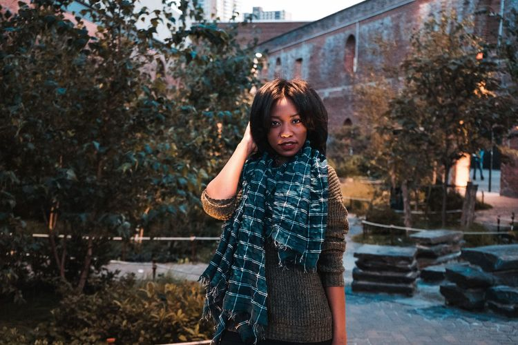 Portrait of teenage girl standing against trees