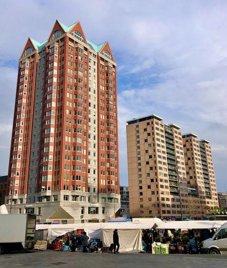 People on street by modern buildings against sky