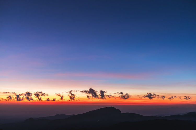 Scenic view of silhouette landscape against sky at sunset