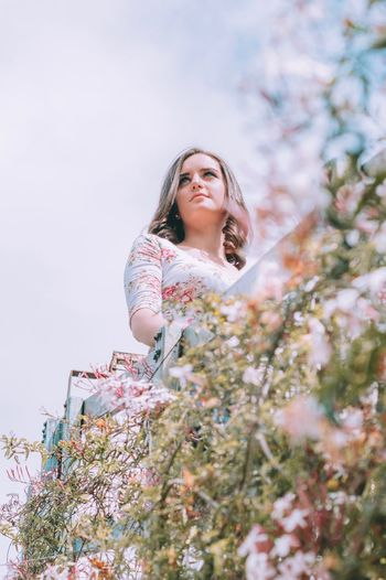 Low angle view of woman by flowering plants against sky